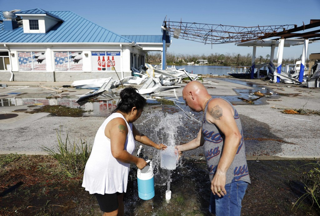 "Danny, right, and Gina Holland collect water in the aftermath of Hurricane Michael in Parker, Fla., Thursday, Oct. 11, 2018. ""We're running out of wat"