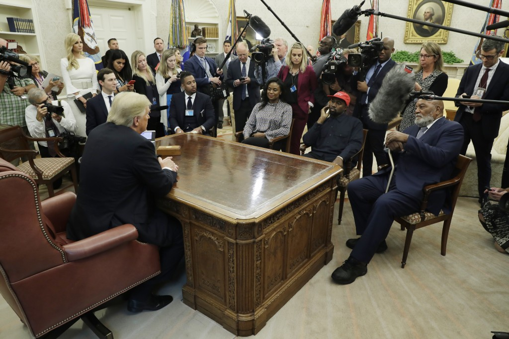 President Donald Trump talks to NFL Hall of Fame football player Jim Brown, seated right, and Rapper Kanye West, seated center, and others in the Oval