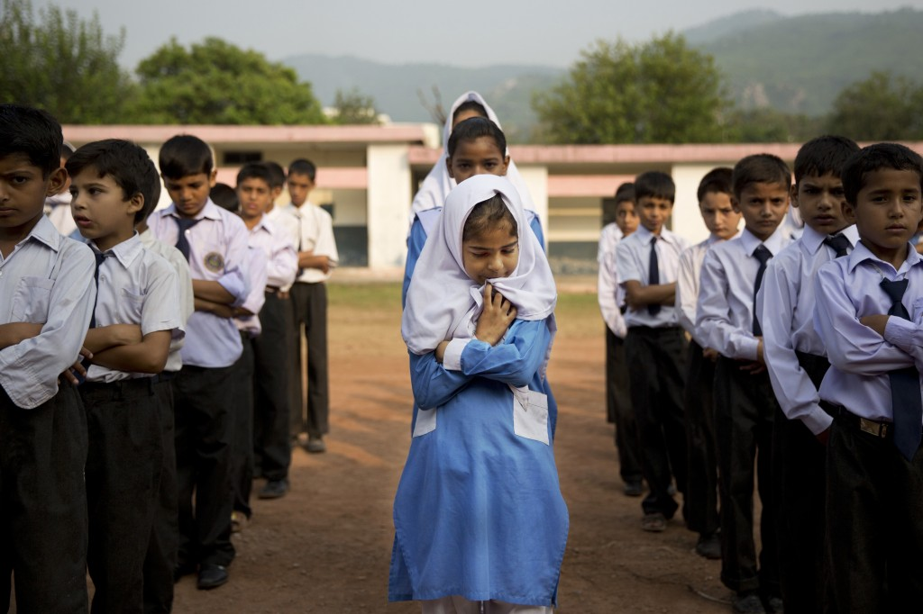 FILE - In this Oct. 11, 2013, file photo, a Pakistani girl lines up among boys for their morning assembly where they sing the national anthem at a sch