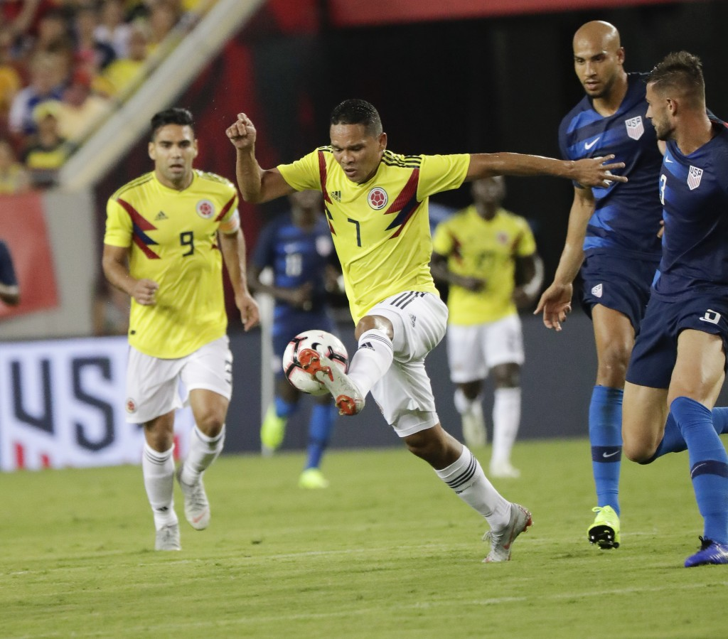 Colombia's Carlos Bacca (7) moves the ball away from United States' John Brooks, center, and Matt Miazga, right, during the first half of an internati