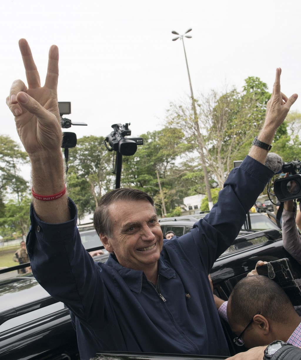 In this Sunday, Oct. 7, 2018 photo, presidential frontrunner Jair Bolsonaro flashes victory hand signs to supporters after voting at a polling station