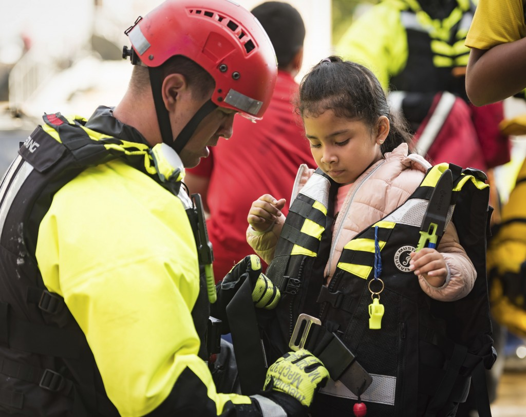 A member of the Winston-Salem Fire Department's water rescue team unzips the life jacket worn by Isabella Molina's, 5, after bringing her from an apar