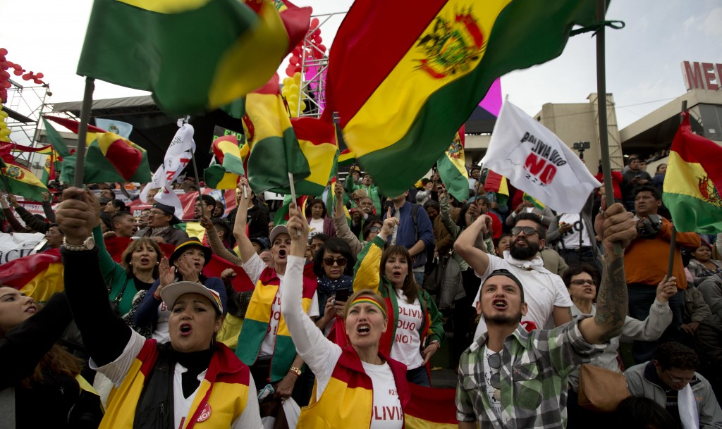 In this Wednesday, Oct. 10, 2018 photo, opponents of President Evo Morales shout slogans and wave national flags as they mark 36 years of democracy, a