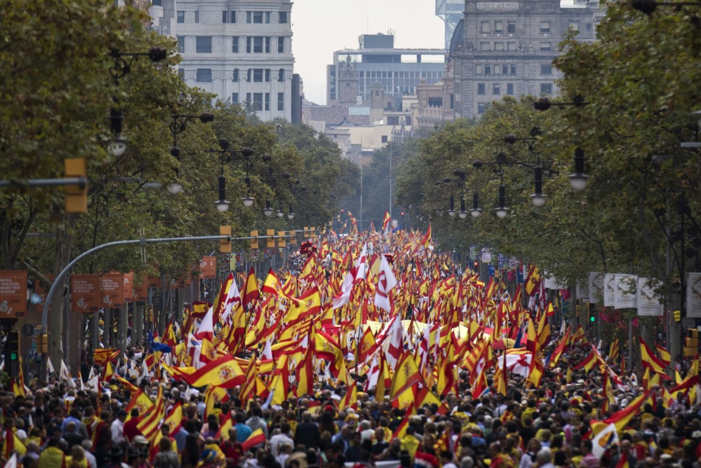 People waving Spanish flags march during Spain's National Day celebrations in the Catalan city of Barcelona, Spain, Friday, Oct. 12, 2018. Catalan pol