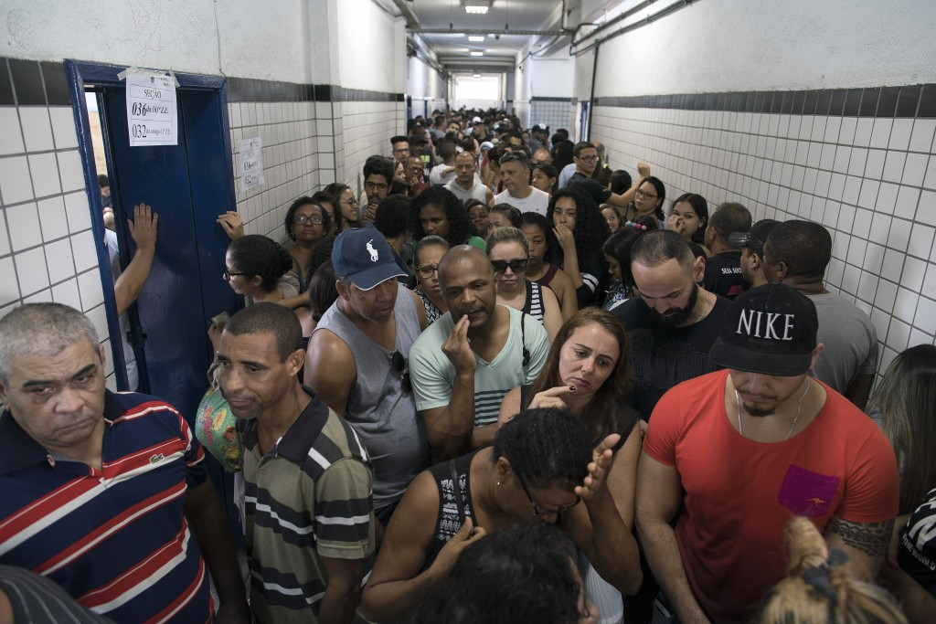 In this Sunday, Oct. 7, 2018 photo, people wait in line to vote in the general election at a polling station in the Mare Complex slum in Rio de Janeir