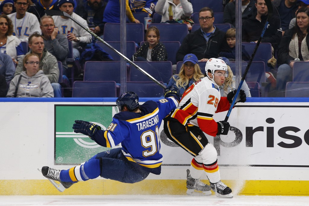 St. Louis Blues' Vladimir Tarasenko, left, of Russia, falls to the ice after colliding with Calgary Flames' Dillon Dube during the first period of an