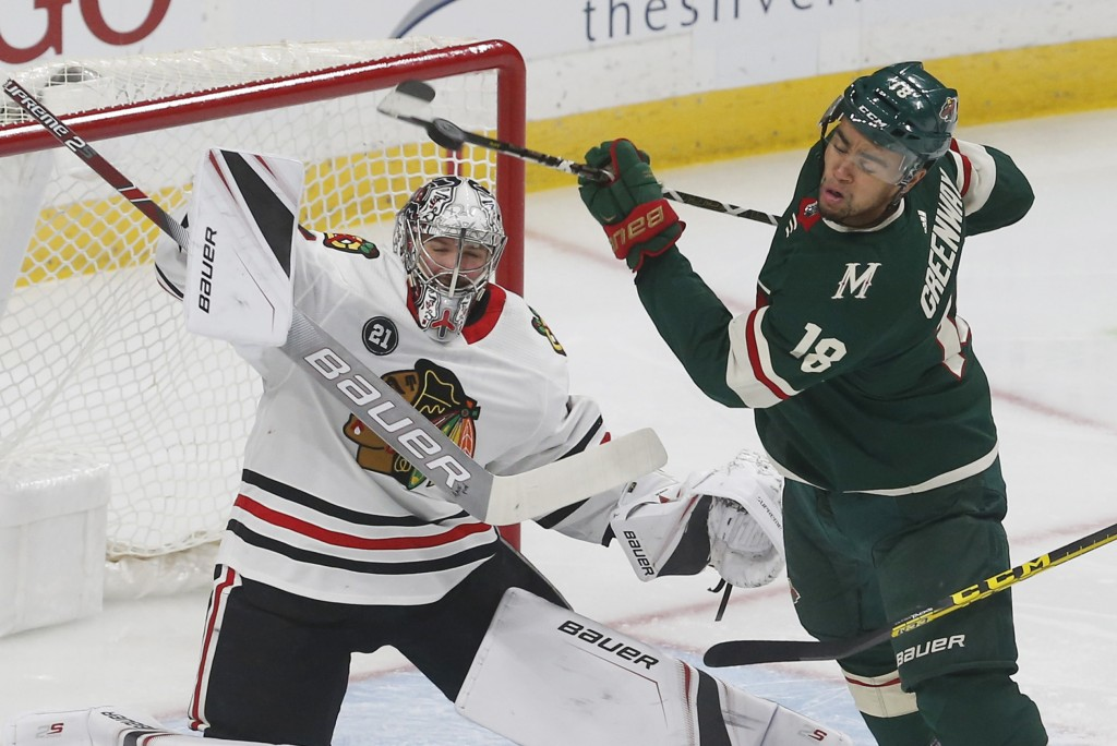 Minnesota Wild's Jordan Greenway, right, gets spun around as Chicago Blackhawks goalie Cam Ward deflects a shot during the first period of an NHL hock