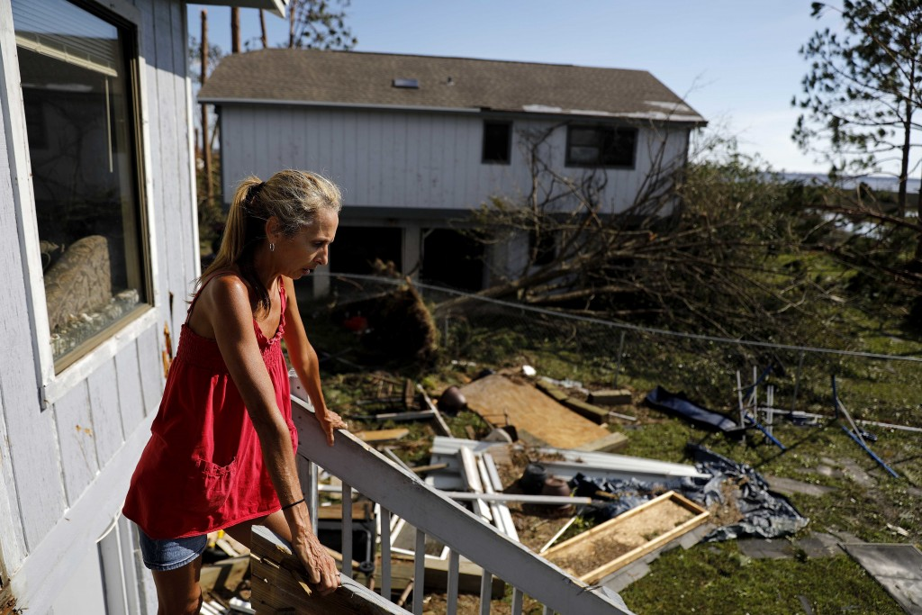 """Monica Jones looks out over the debris littering her yard after riding out hurricane Michael in her home in Callaway, Fla., Thursday, Oct. 11, 2018. """""""