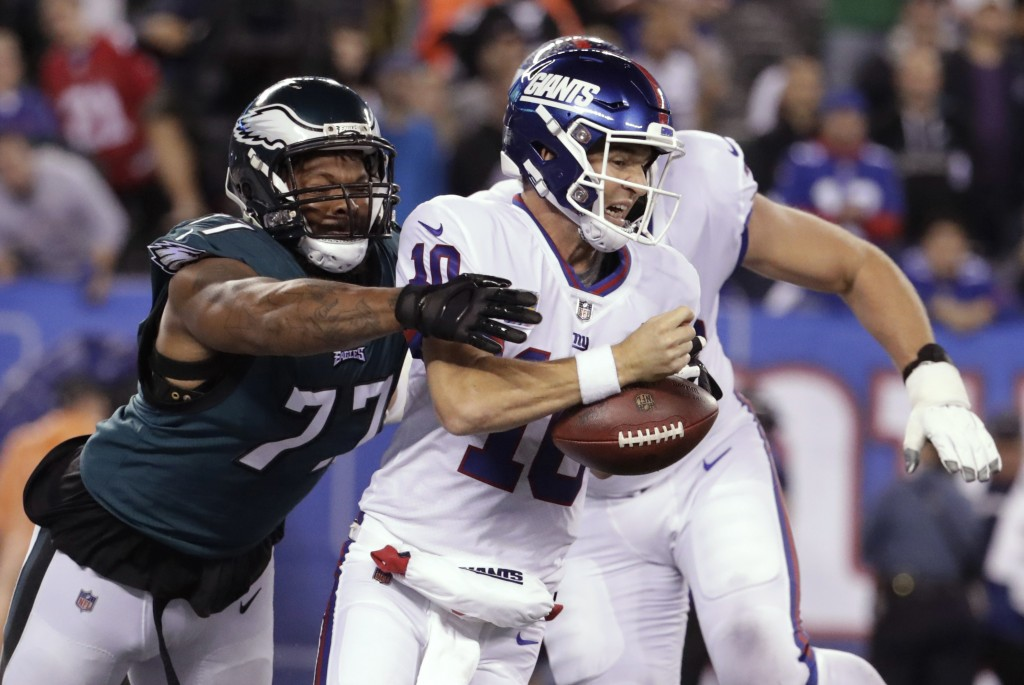 Philadelphia Eagles defensive end Michael Bennett (77) strips the ball from New York Giants quarterback Eli Manning during the first half of an NFL fo