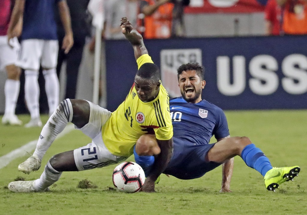 Colombia's Deiver Machado (21) and United States' Kenny Saief, right, fall while going for the ball during the second half of an international friendl