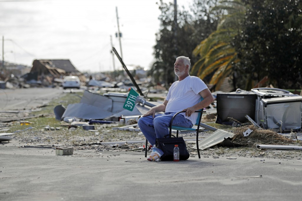 Resident Tony Feller, who stayed in Mexico Beach, Fla., during Hurricane Michael, sits in a chair amidst the destruction, Thursday, Oct. 11, 2018. (AP