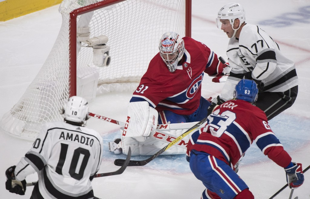 Montreal Canadiens goaltender Carey Price (31) is pressured by Los Angeles Kings' Michael Amadio (10) and Jeff Carter (77) as Canadiens' Matthew Peca