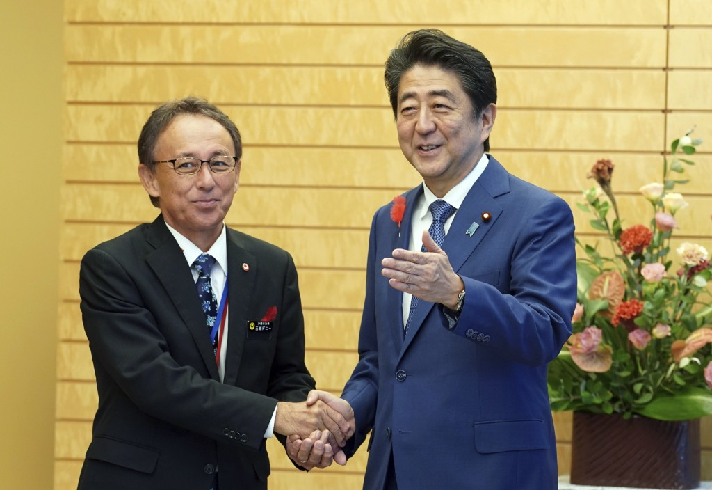 Okinawa Gov. Denny Tamaki, left, and Japanese Prime Minister Shinzo Abe shake hands during a meeting at Abe's office in Tokyo Friday, Oct. 12, 2018. T