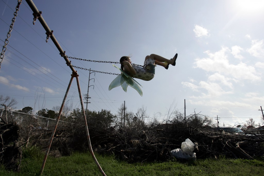FILE - In this Feb. 25, 2006, file photo, Nysa Loudon, 11, swings in the neighborhood park ravaged by Hurricane Katrina near her home in Gentilly area