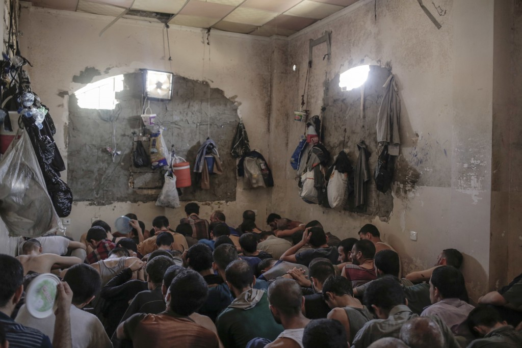 FILE - In this Tuesday, July 18, 2017, file photo, suspected Islamic State members sit inside a small room in a prison south of Mosul, Iraq. With Isla