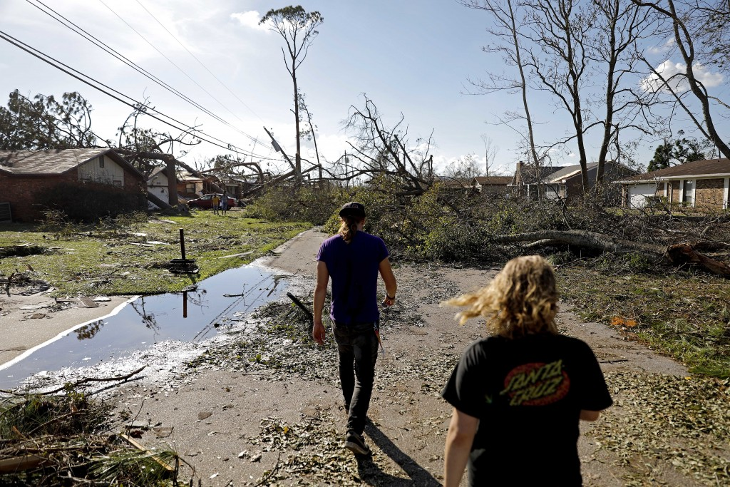 Kelsey Gronbeck, right, and Spencer Hall walk through a damaged neighborhood after checking on he home of Hall's father in the aftermath of hurricane