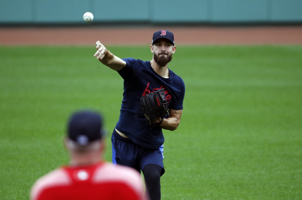 Boston Red Sox pitcher Rick Porcello throws as pitching coach Dana LeVangie watches during a baseball workout, Thursday, Oct. 11, 2018, in Boston. The