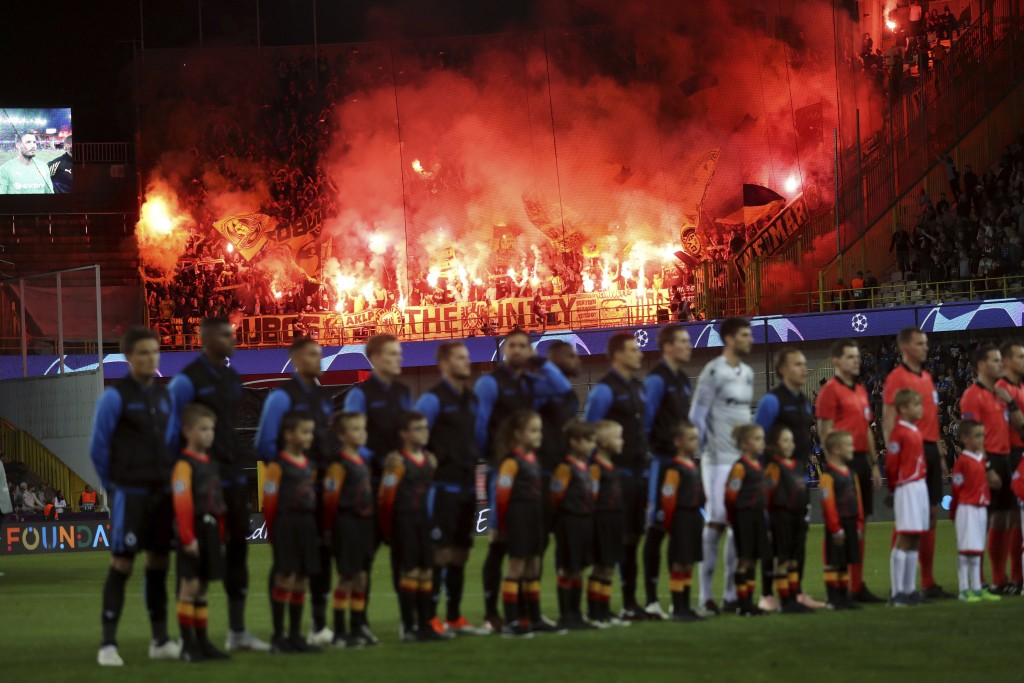In this photo taken on Tuesday, Sept. 18, 2018 Dortmund fans set off flares as Club Brugge players stand on the pitch prior their Champions League gro