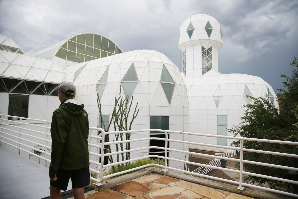 In this July 31, 2015 photo,  a tourist walks to the main entrance of the Biosphere 2 facility while on a walking tour in Oracle, Ariz. University of