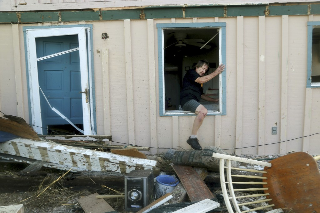 James Murphy emerges from what remains of his home on Thursday, Oct. 11, 2018, on a coastal stretch of Port St. Joe, Fla. The home was severely damage