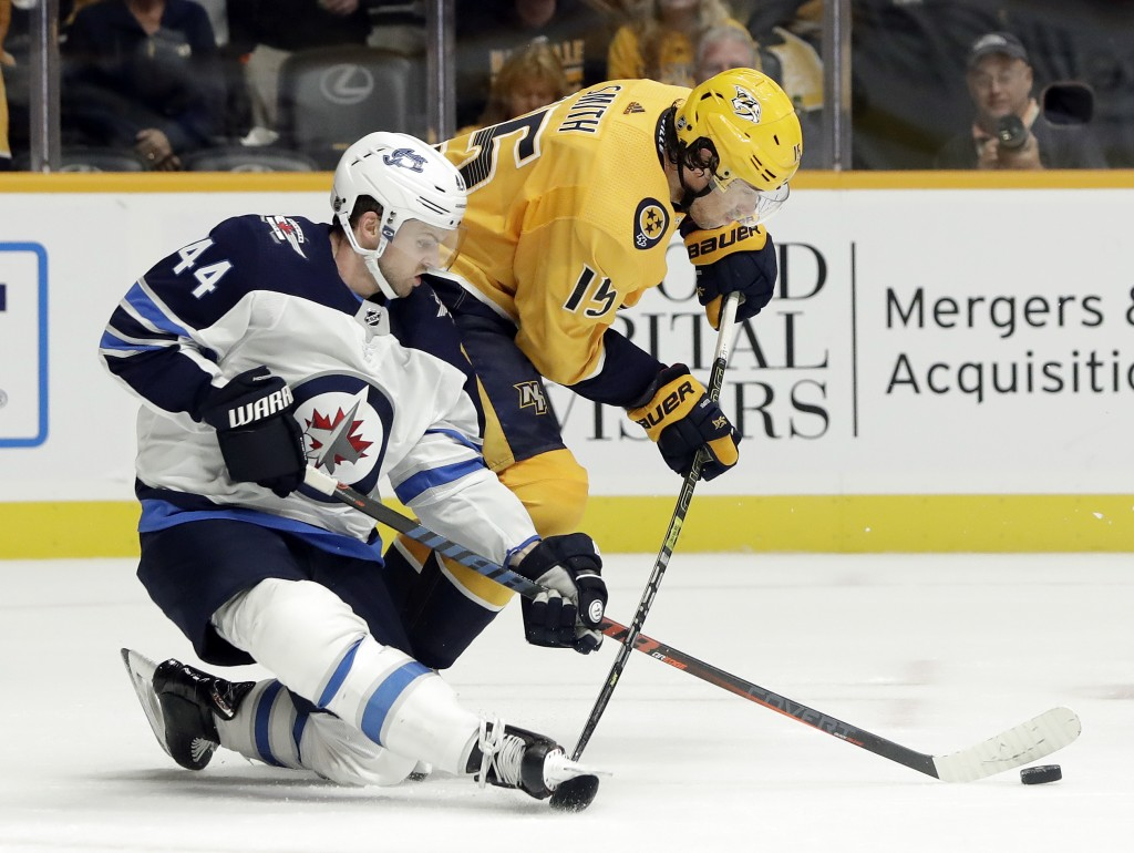 Winnipeg Jets defenseman Josh Morrissey (44) battles Nashville Predators right wing Craig Smith (15) for the puck during the second period of an NHL h