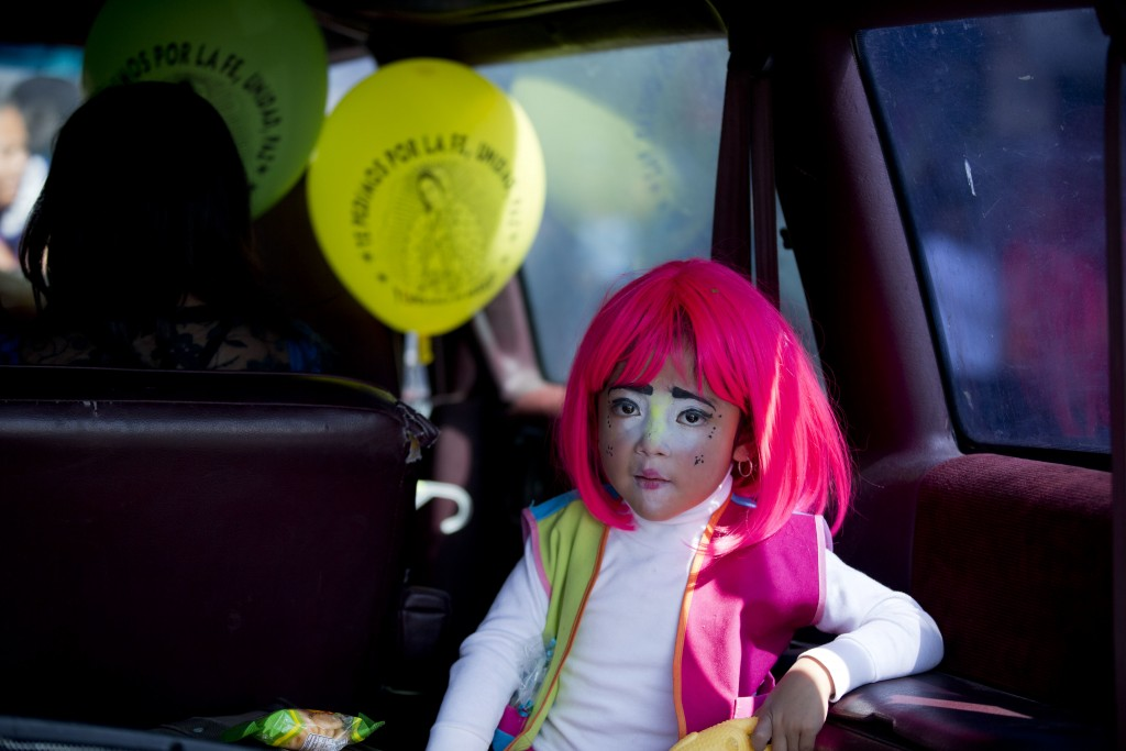 FILE - In this Dec. 14, 2015, file photo, a young clown rides in the back of a car following a procession to the Basilica of Our Lady of Guadalupe in