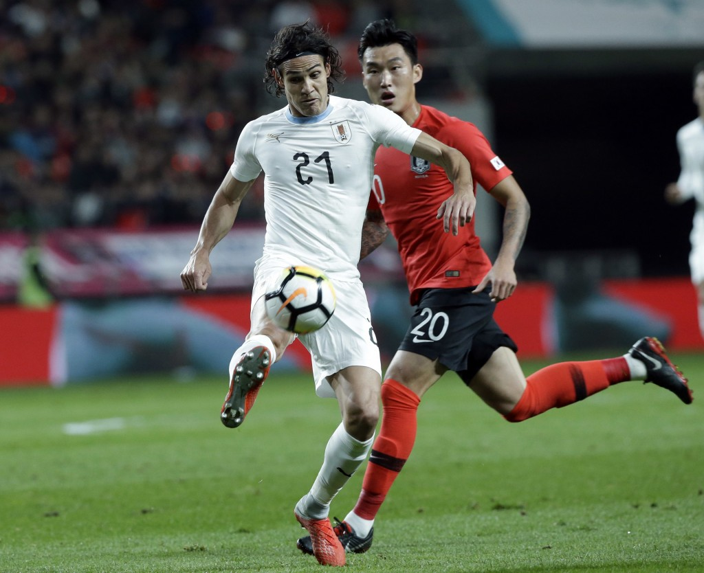 Uruguay's Edinson Cavani, left, fights for the ball against South Korea's Jang Hyun-soo during their friendly soccer match in Seoul, South Korea, Frid