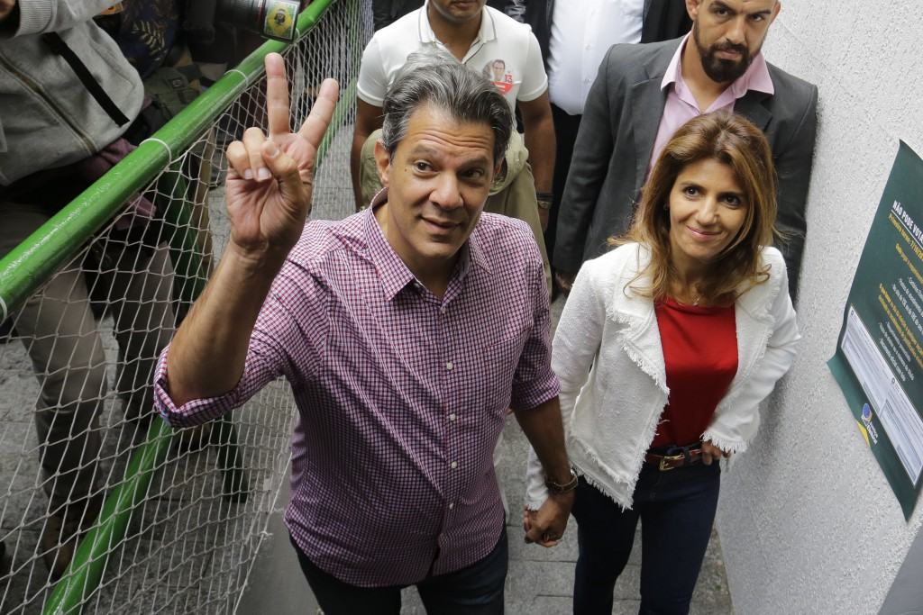 In this Sunday, Oct. 7, 2018 photo, Workers' Party presidential candidate Fernando Haddad, accompanied by his wife Ana Estela, arrives at a polling st