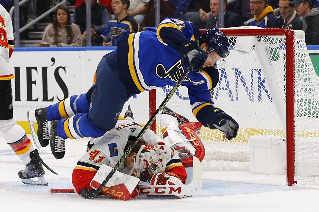 St. Louis Blues' Vladimir Tarasenko, top, of Russia, is tripped up by Calgary Flames goaltender Mike Smith, who covers the puck during the second peri
