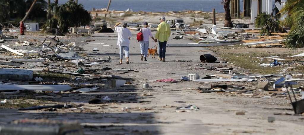 People hold hands as they walk amidst destruction in the aftermath of Hurricane Michael in Mexico Beach, Fla., Thursday, Oct. 11, 2018. (AP Photo/Gera