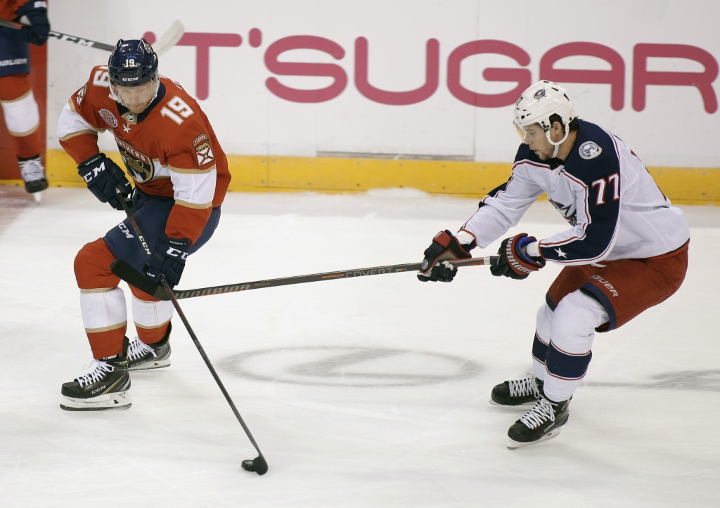 Florida Panthers defenseman Mike Matheson (19) and Columbus Blue Jackets right wing Josh Anderson (77) compete for the puck during the first period of