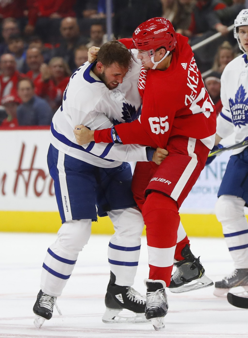 Toronto Maple Leafs left wing Josh Leivo (32) and Detroit Red Wings defenseman Danny DeKeyser (65) fight during the first period of an NHL hockey game