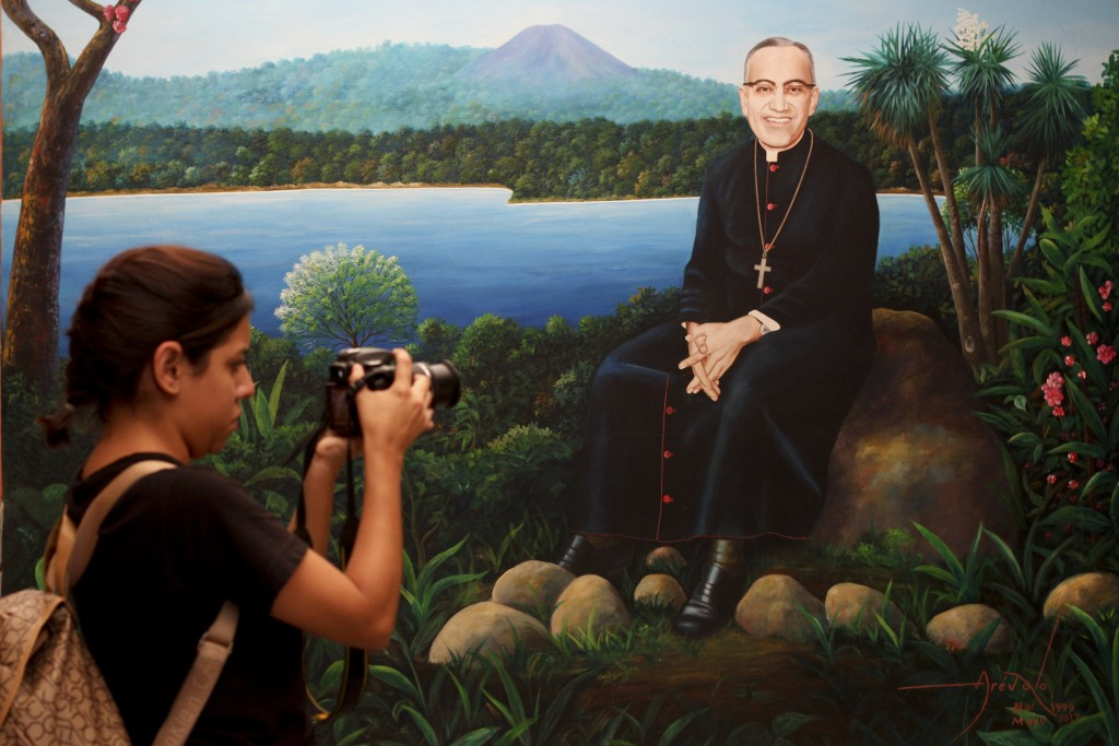 In this Oct. 5. 2018 photo, a woman takes photographs of a mural of Archbishop Oscar Arnulfo Romero, located at the Monsignor Romero Historic Center,