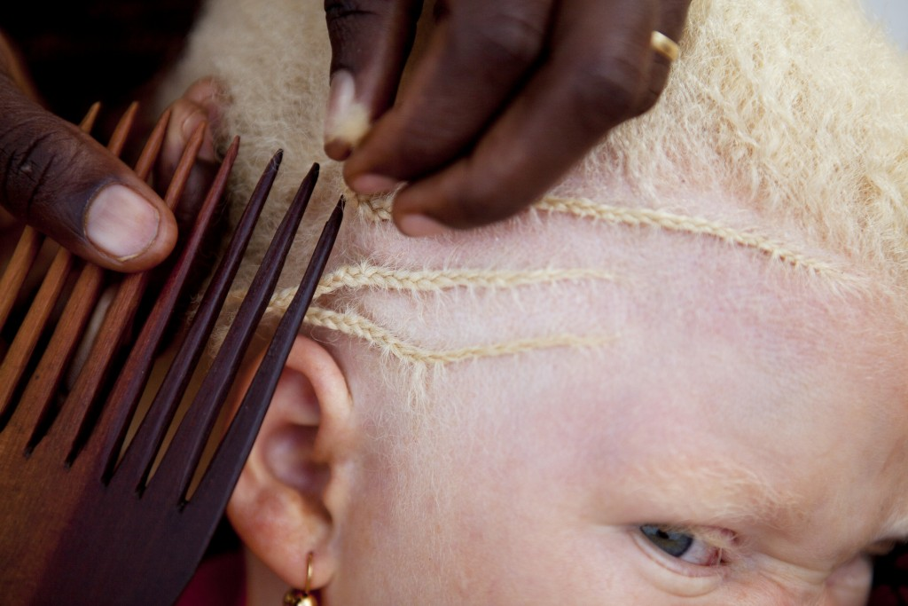 In this Aug. 27, 2012 photo, Janet Jotham braids the hair of her daughter Lucia Jotham, 8, during a visit to see her two children living at the Kabang