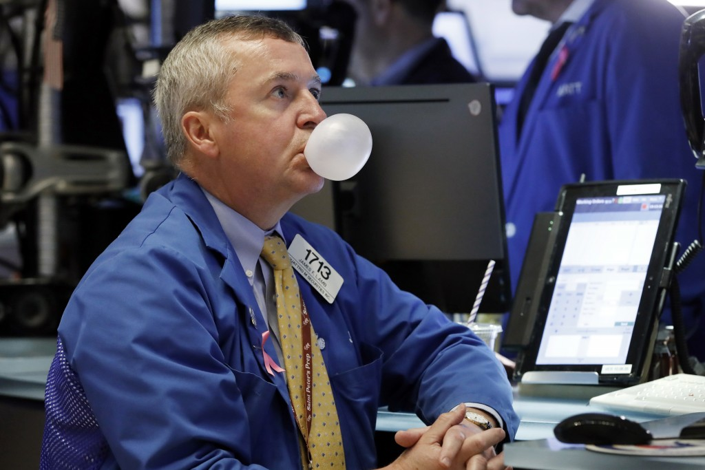FILE- In this Oct. 10, 2018, file photo trader James Lamb watches his screens on the floor of the New York Stock Exchange. After a harrowing week for