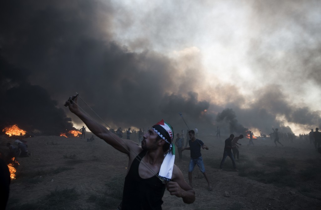 A Palestinian protester slings stones toward Israeli troops during a protest at the Gaza Strip's border with Israel, Friday, Oct. 12, 2018. (AP Photo/