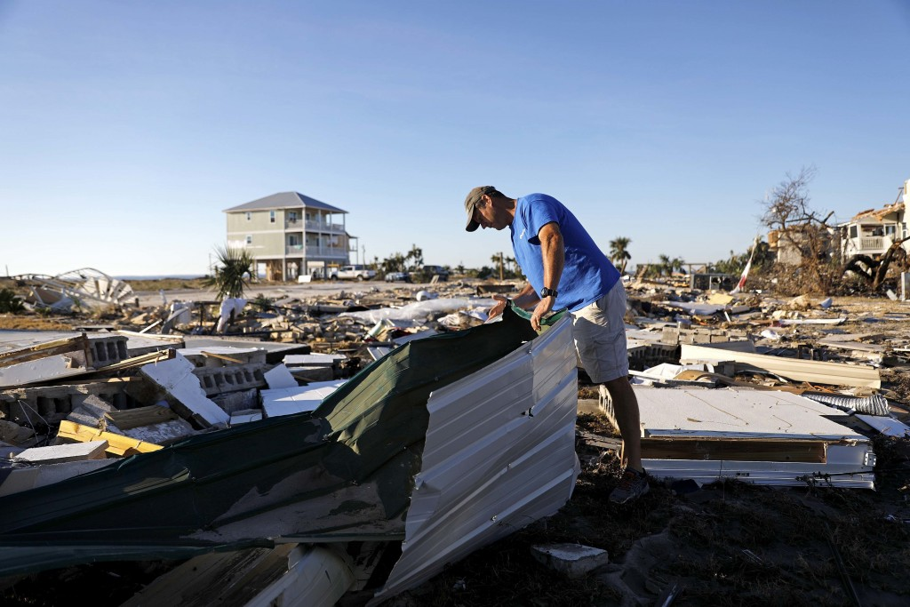 Mike Jackson sifts through debris looking for remnants of his home which was destroyed by hurricane Michael in Mexico Beach, Fla., Saturday, Oct. 13,