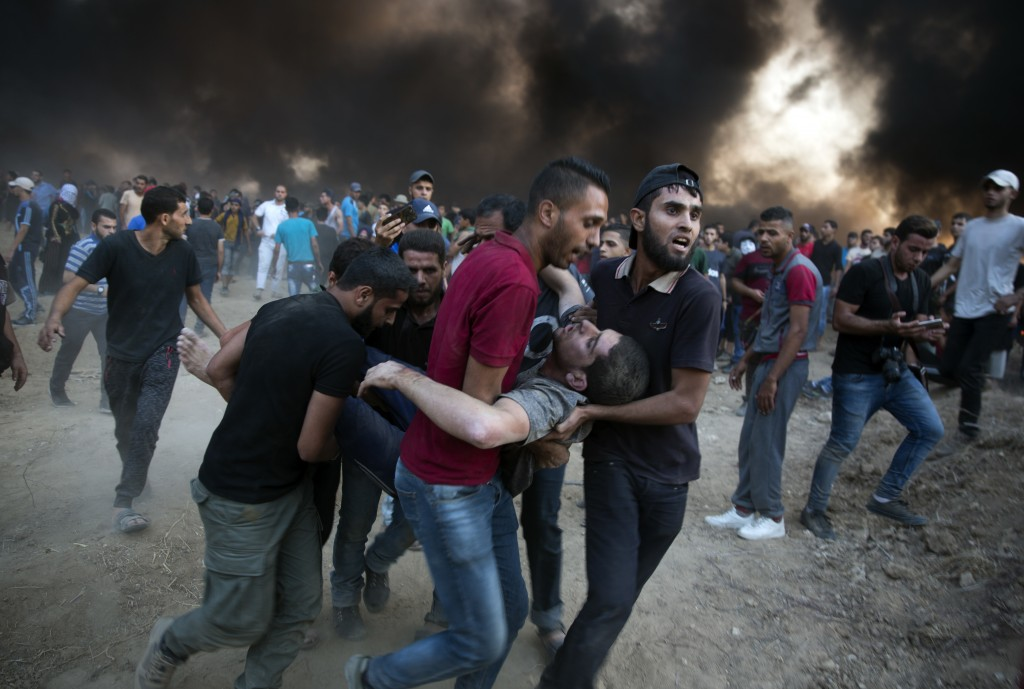 Palestinian protesters evacuate a wounded man was shot by Israeli troops during a protest at the Gaza Strip's border with Israel, Friday, Oct. 12, 201