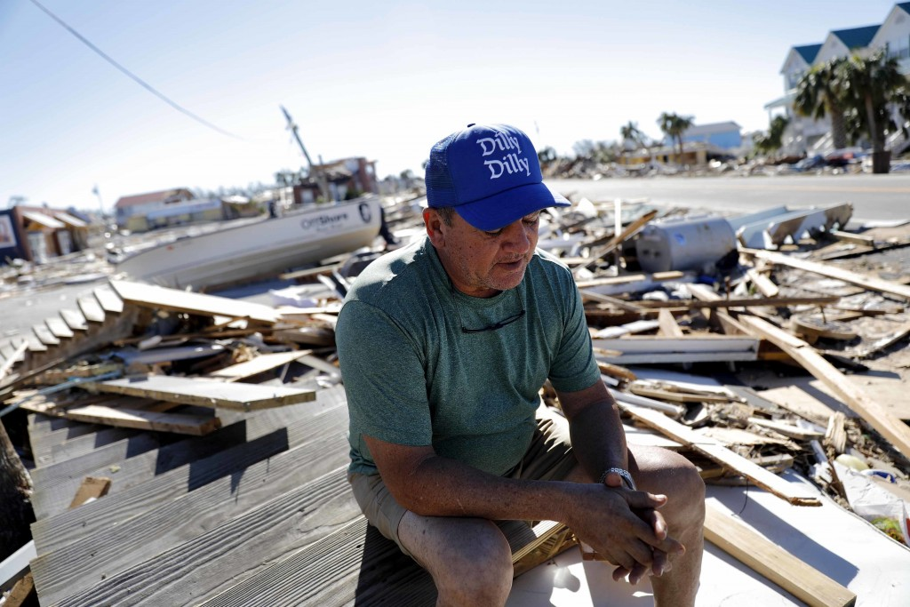 """Hector Morales sits on a debris pile near his home which was destroyed by Hurricane Michael in Mexico Beach, Fla., Friday, Oct. 12, 2018. """"I have noth"""