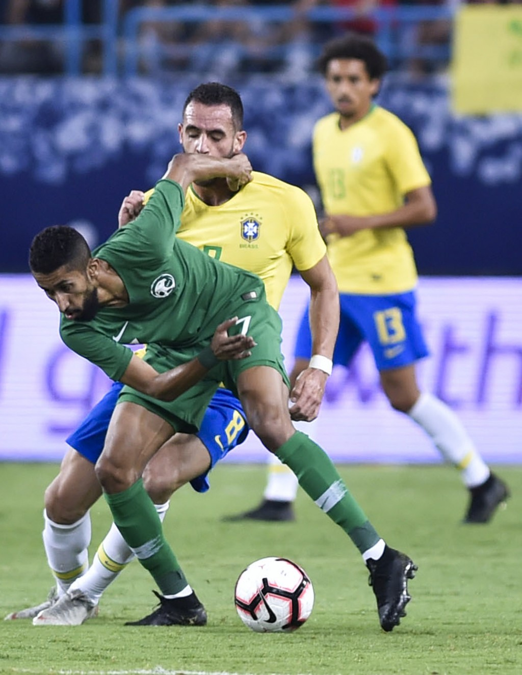 Saudi Arabia's Salman Alfaraj, left, competes for the ball with Brazil's Renato during a friendly soccer match between Brazil and Saudi Arabia at King