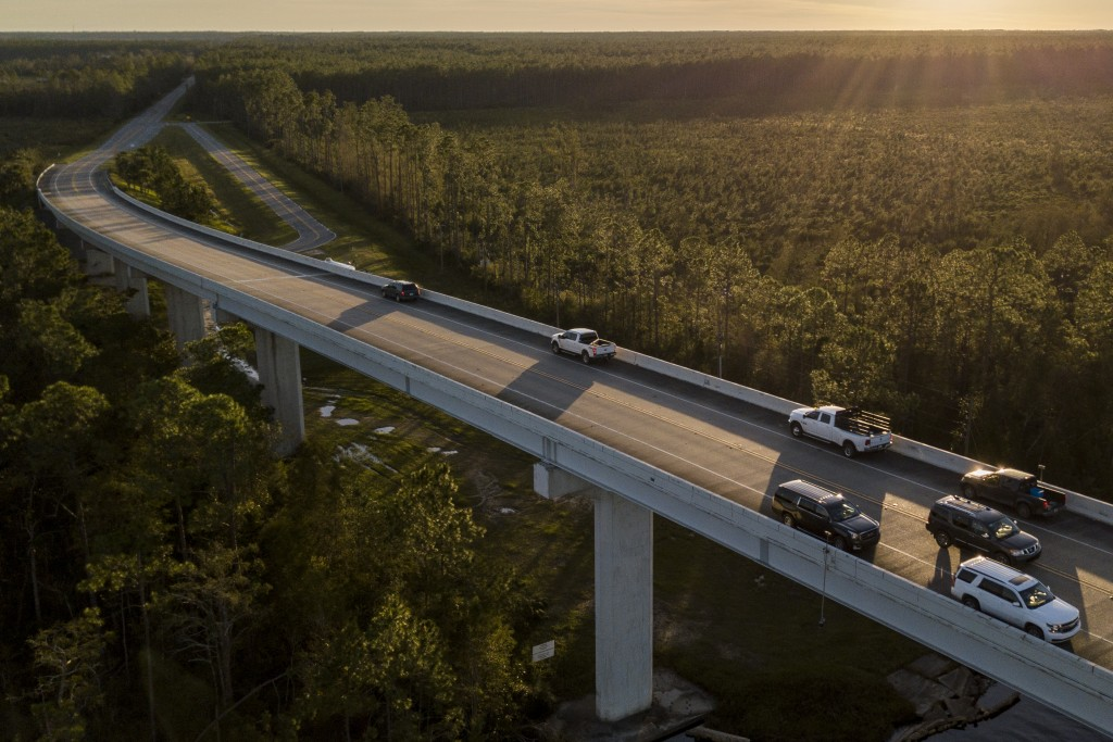Vehicles sit parked on a bridge while drivers try to reach a phone signal on Highway 71 near Port St. Joe, Fla., Friday, Oct. 12, 2018, after Hurrican