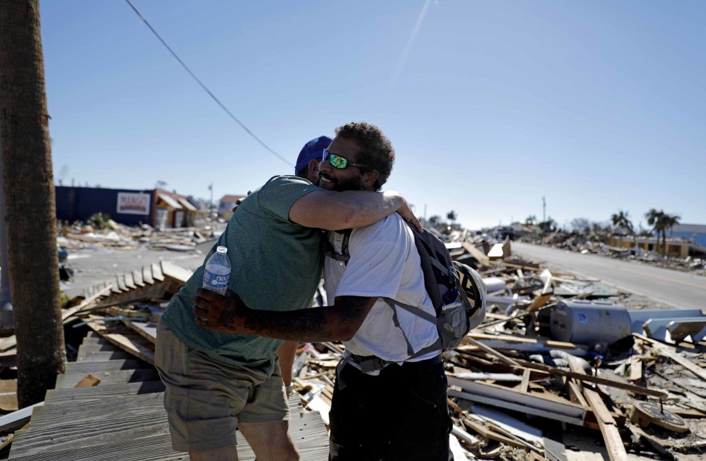 Hector Morales, left, is hugged by friend Matthew Goss, a fisherman, as they reunite after Hurricane Michael which destroyed Morales' home and Goss' b