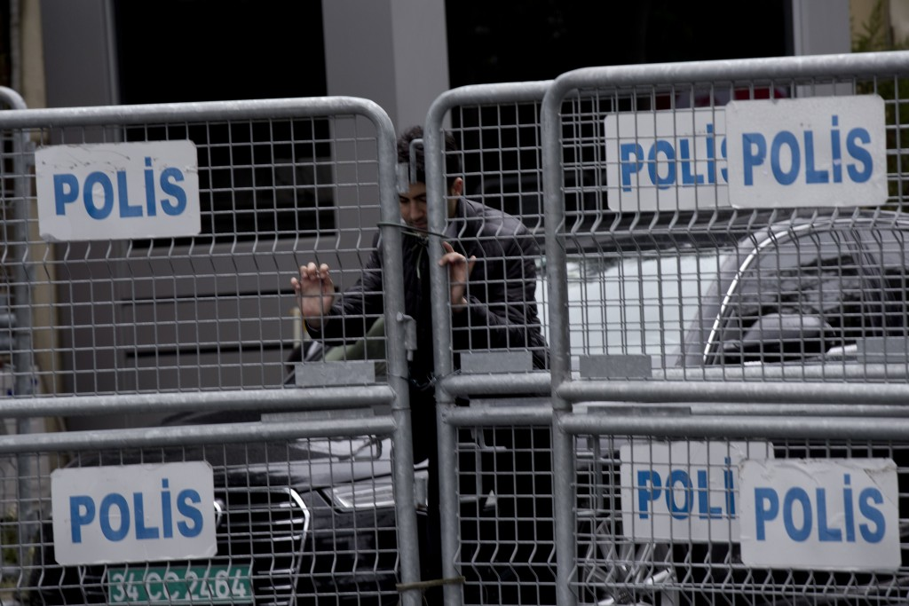 A security personnel places metal barriers at the entrance of Saudi Arabia's consulate in Istanbul, Saturday, Oct. 13, 2018. Turkish officials have an