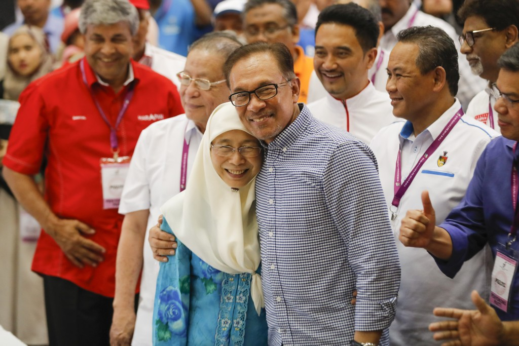 Malaysia's politician Anwar Ibrahim, right, hug his wife while Deputy Prime Minister Malaysia Wan Azizah Ismail celebrates after winning the by electi