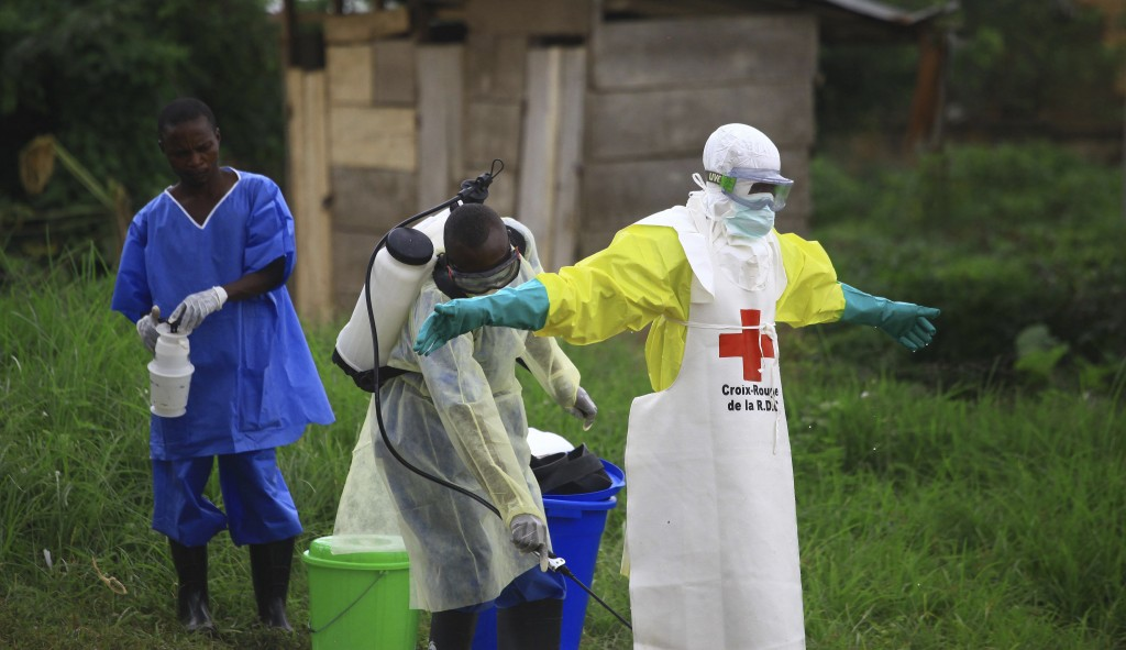 FILE - In this Sept. 9, 2018, file photo, a health worker sprays disinfectant on his colleague after working at an Ebola treatment center in Beni, Eas