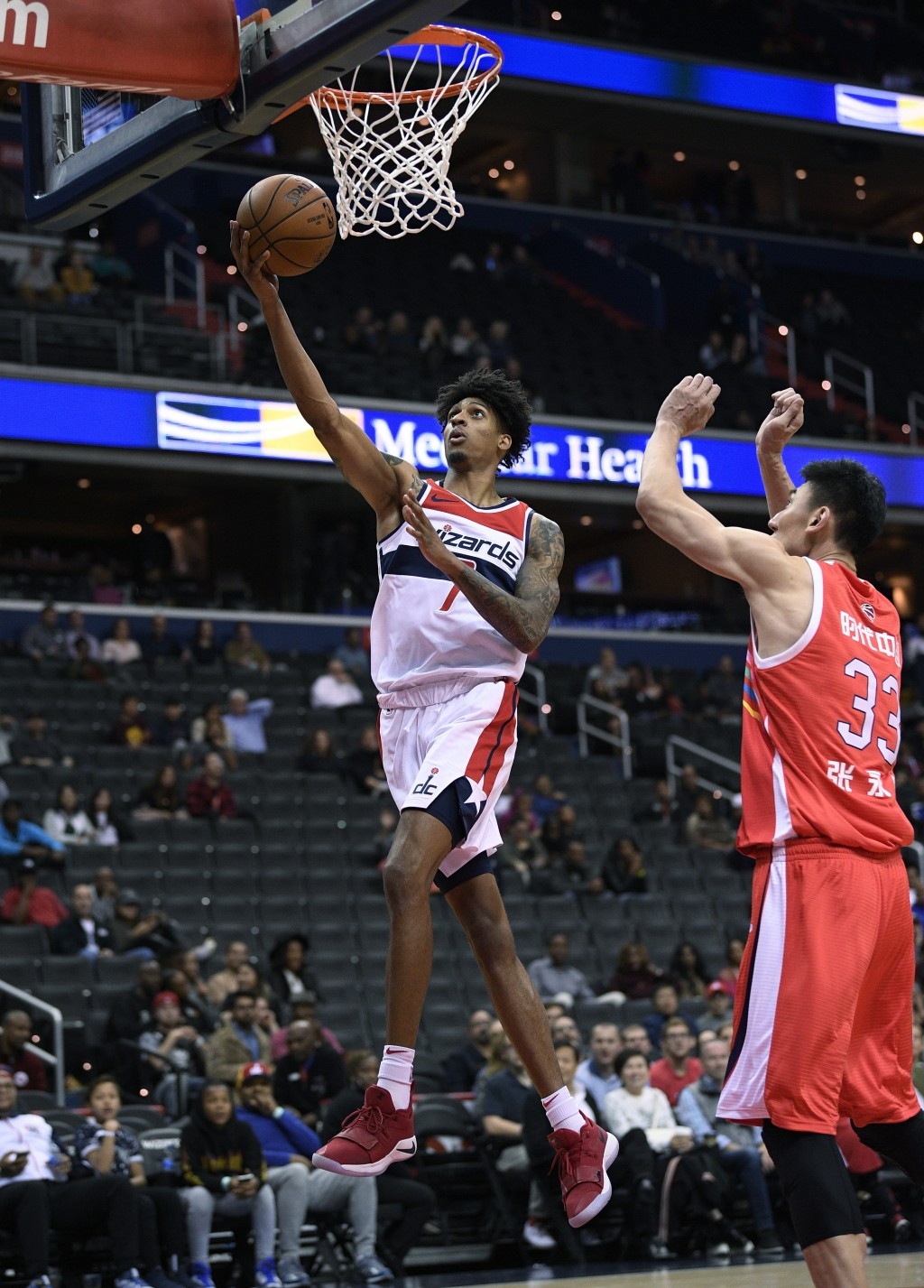 Washington Wizards forward Devin Robinson (7) goes to the basket past Guangzhou Long-Lions center Yongpeng Zhang (33) during the second half of an NBA