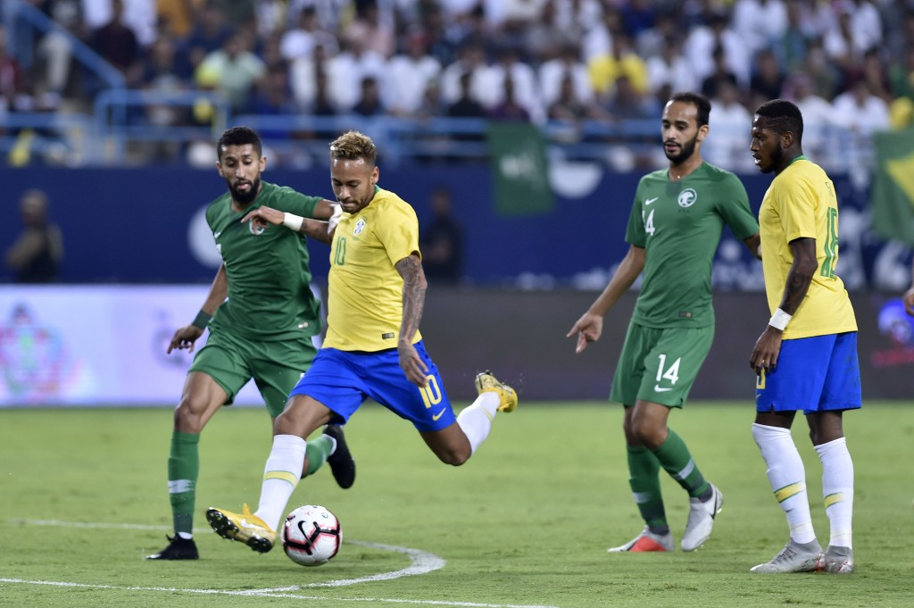 Brazil's Neymar, second left, shots the ball as Saudi Arabia's Hussain Almoqahwi, left, tries to block the ball during a friendly soccer match between