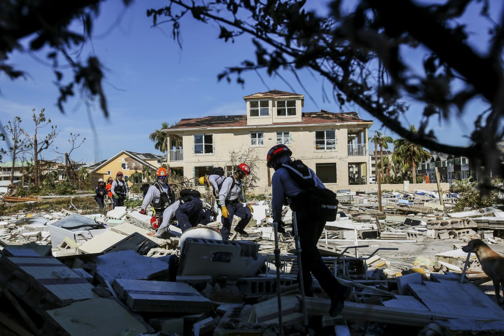 Members from South Florida Task Force search a flattened home destroyed by Hurricane Michael in Mexico Beach, Fla., Friday, Oct. 12, 2018, after Hurri