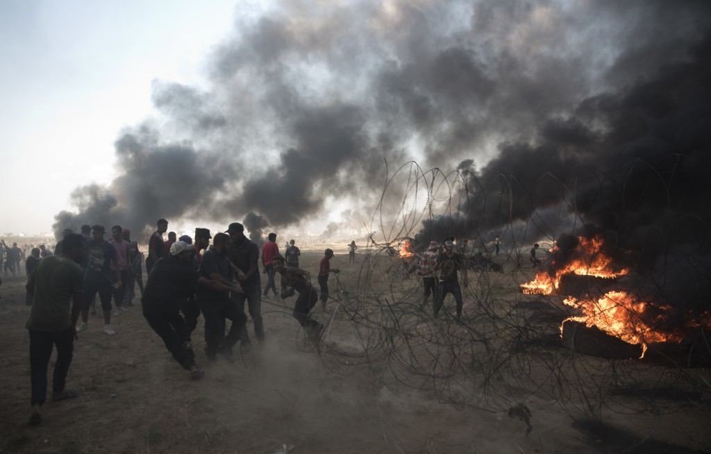 Palestinian protesters pull barbed wire during a protest at the Gaza Strip's border with Israel, Friday, Oct. 12, 2018. (AP Photo/Khalil Hamra)