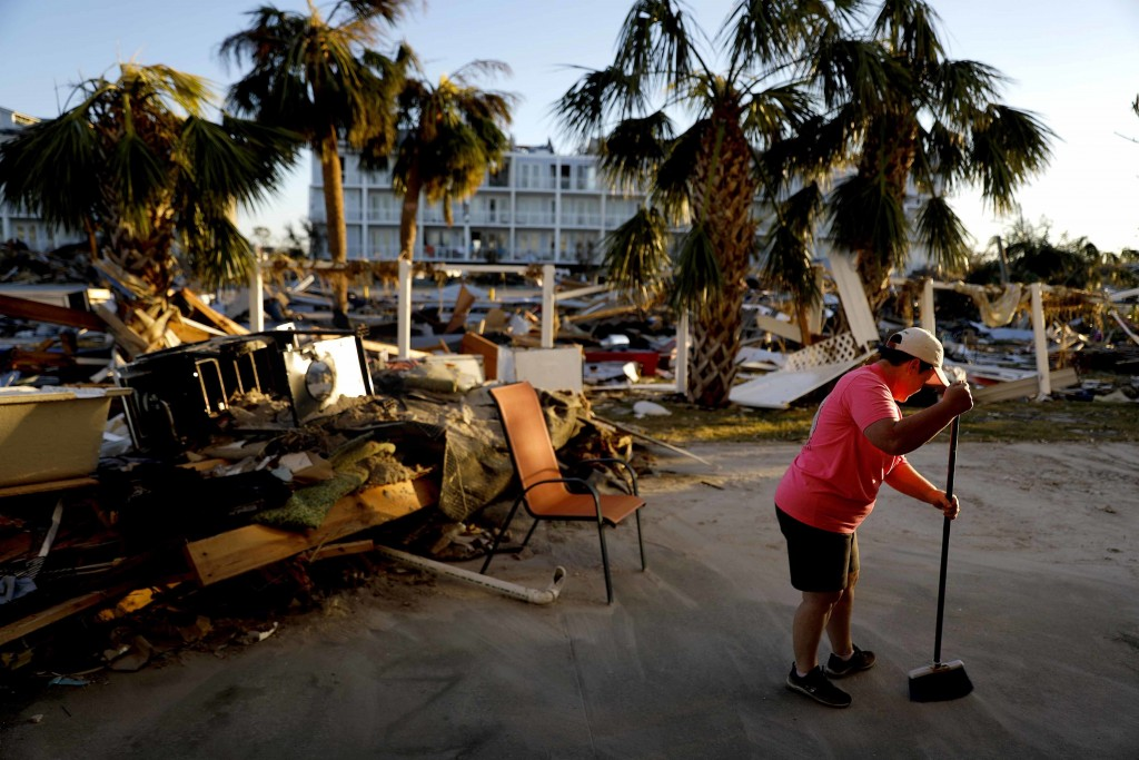 Peggy Cauley cleans up debris from her family's home in the aftermath of hurricane Michael in Mexico Beach, Fla., Saturday, Oct. 13, 2018. (AP Photo/D